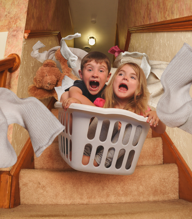 Two young children are riding in a laundrey basket down the house stairs with socks flying for a parenting, babysitter or humor concept.