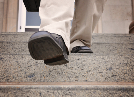 office shoes: A business man is stepping down the stairs at an office for a power, challenge or motivation concept.