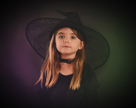 A little girl is wearing a halloween costume as a scary witch on a black isolated background. Banco de Imagens