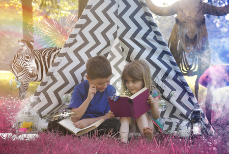 storytime: Little Children are reading an old story book in a teepee with purple grass and animals for an education or imagination concept. Stock Photo