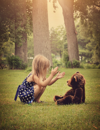 stuffed animals: A little girl is clapping her hands and playing with a teddy bear outside at a park for a friendship or imagination concept.