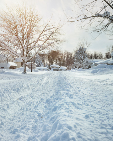 ny: A long road and houses are covered with deep white snow in western new york for a weather or blizzard concept.