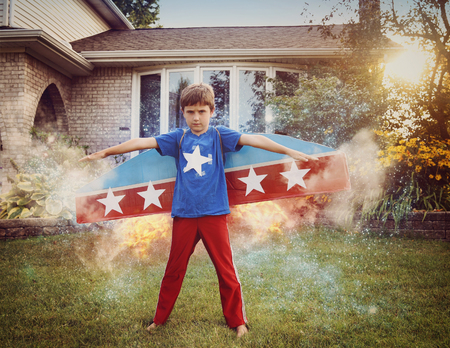 imagining: A young boy is wearing cardboard rocket wings with stars on the costume. He is in the front yard imagining he is in space with stars flying.