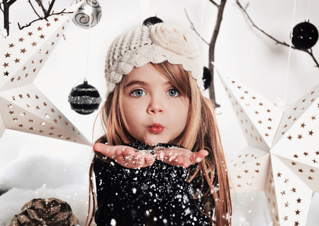 and in winter: A young child is blowing white snowflakes in a studio background scene with stars and christmas ornaments for a holdiay concept. Stock Photo