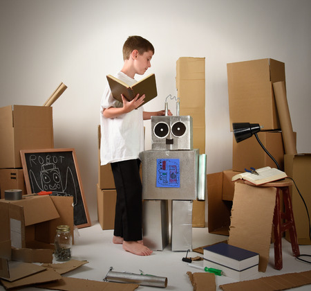 A child is reading a book and building a metal robot from cardboard boxes on white for an imagination, science or education concept.
