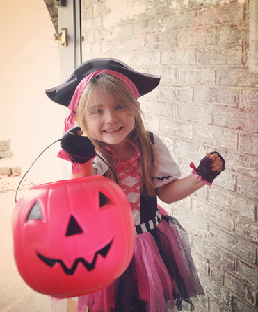 A little girl is dressed up in a pink pirate costume trick or treating at a door with a pumpkin basket and smiling. Banco de Imagens