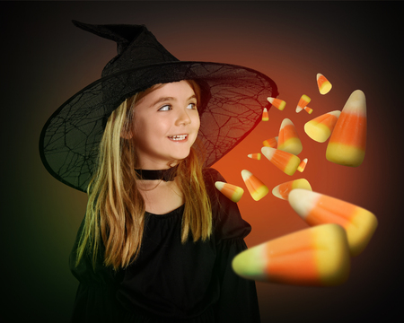 A little girl is wearing a witch halloween costume with a black hat. The child is imaginaing candy corn for a halloween or trick or treat concept.