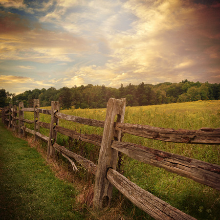 An Old Rustic Wooden Fence Is In A Grass Filed With Trees And Clouds The