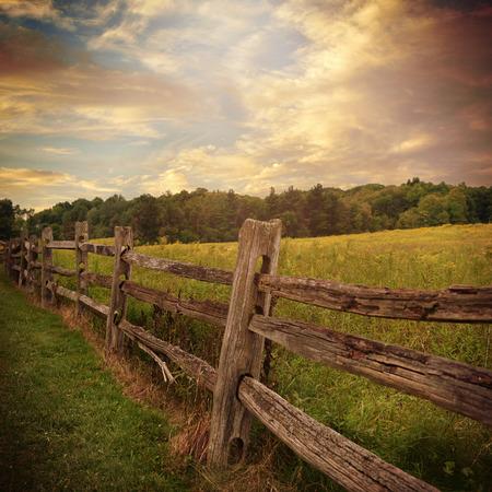 krajina: Starý rustikální dřevěný plot je v trávě podané stromy a mraky na pozadí pro koncepci zemi nebo přírody.