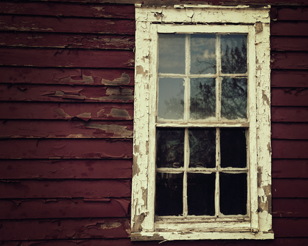A scary dark wooden window on a house with peeling red paint for a fear or danger crime concept.