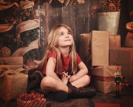 girl looking up: A little girl is sitting on a wooden floor with christmas decorations and presents looking up and makeing a wish for a holiday or seasonal concept.