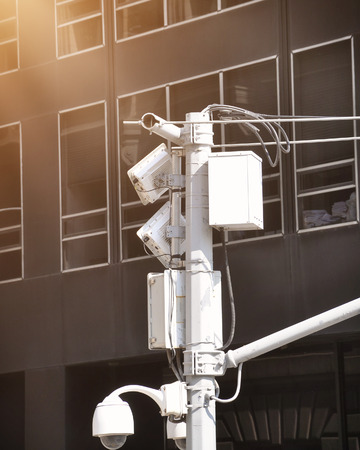 A security video surveillance camera is high in the sky with a city building in the background for a safety concept