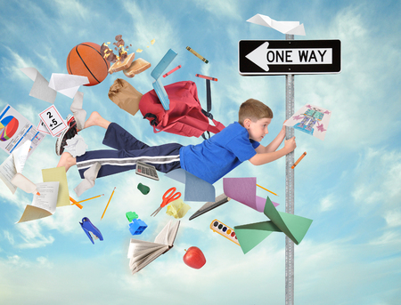 A young boy is holding on to a one way direction sign with school supplies flying around him for an education activity or speed concept