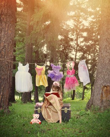 book concept: A little girl is dressed up as a princess reading a book in the woods with costumes hanging from a clothesline for an education or fantasy concept.