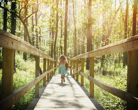小さな子供は、自由または冒険の概念の日光の光線が付いている木と森の中で木道の上実行しています。