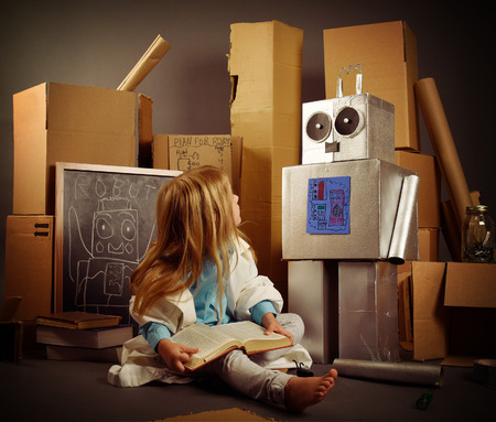 A science student is inventing a metal robot out of cardboard boxes with tools. Use it for an education or imagination concept. 版權商用圖片