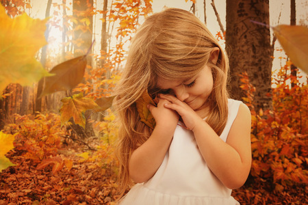 A little girl is holding onto a fall leaf in the woods with sunlight in the background and falling leaves for a season or nature concept
