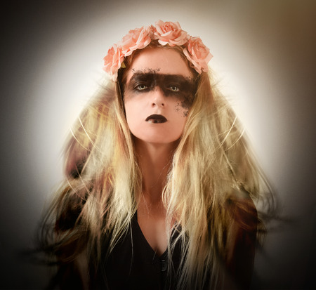 A scary dark woman has smokey black eyes and black lips with a flower headpiece and blonde hair blwoing on a whiet background for a halloween or fear concept. Фото со стока