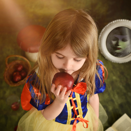 A little child is holding an apple with an evil witch in the background in the forest for a magical snow white fairy tale concept story.