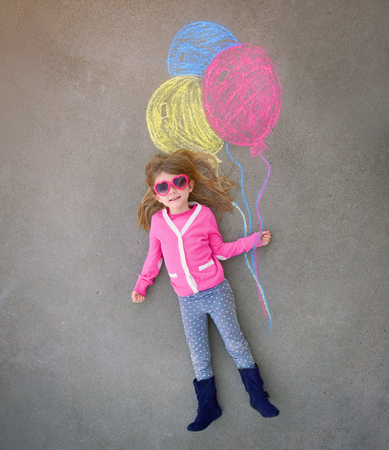 A cute little girl with sunglasses is holding creative chalk balloons drawn on the sidewalk cement for a imagination, summer or activity concept.
