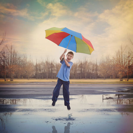 A boy is jumping high in the air up to the sky with a rainbow umbrella and a rain puddle with a splash of water for a happiness or spring concept.