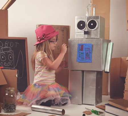 A little child is building and fixing a robot with boxes and tools for a girl power, education or imagination concept.