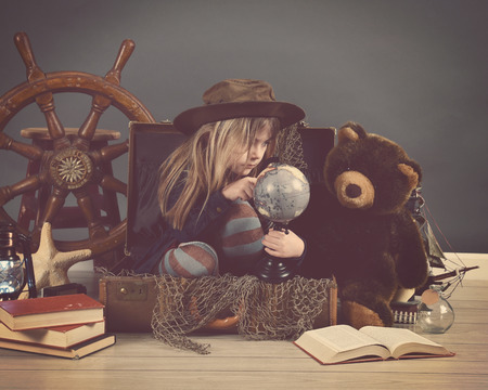 A little child is sitting in a travel suitcase looking at a globe with sea props for an imagination or education concept.
