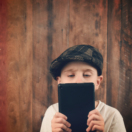 electronic tablet: A boy is holding a technology tablet and reading a screen. The chikld is wearing a vintage cap with a wood background for a communication or electronic idea. Stock Photo