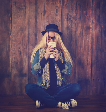 A young hipster woman is drinking a hot coffee drink against a wood background. She has glasses and a hat on for a beverage concept. Фото со стока