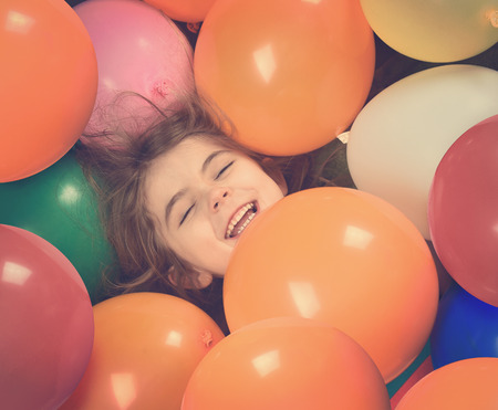 child birthday: A little child is in a bunch of colorful balloons laughing for a birthday party or celebration concept.