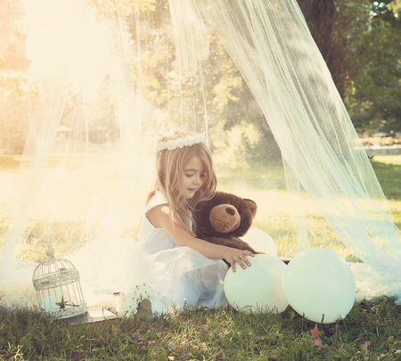 A beautiful little girl is playing with balloons in a white dress outside under a canopy with sunlight for a spring or summer concept.