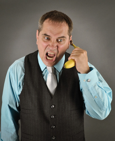 business metaphore: An angry business man is talking on a banana phone on an isolated gray background for a humorours communication health concept. Stock Photo