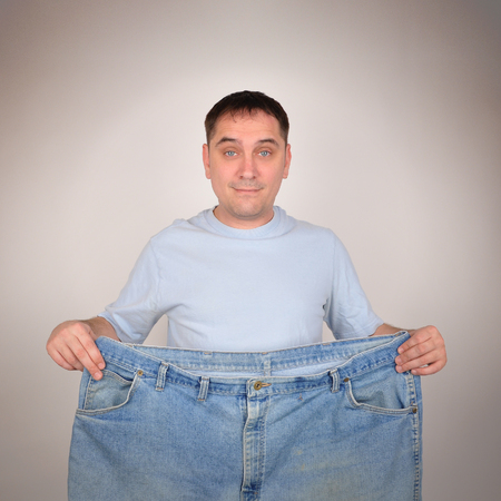 A man is holding up a pair of big large pants for a before and after weight loss concept. He is isolated on the background.