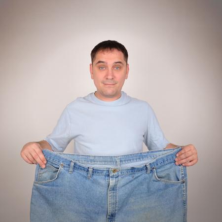Un hombre es la celebración de un par de pantalones grandes grandes para un concepto antes y después de la pérdida de peso. Se aisló en el fondo. Foto de archivo