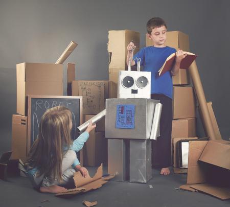 2 人の子供は、想像力、科学または教育概念のツールや書籍を段ボール箱から金属製のロボットを構築しています。