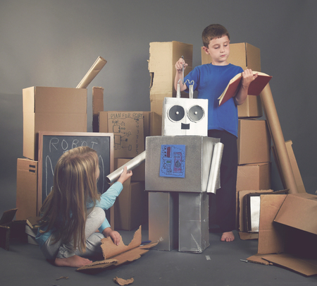 Two Children are building a metal robot from cardboard boxes with tools and books for an imagination, science or education concept.