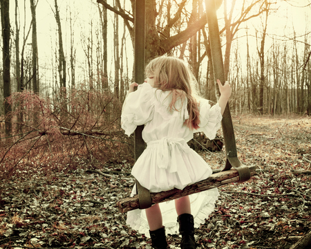 A little girl is alone swinging on an old vintage swing in the woods with trees for a fear, hope or sadness concept Foto de archivo