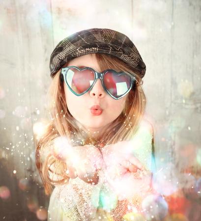 작은 아이 선글라스 착용 하 고 축 하, 행복 또는 파티 아이디어에 대 한 공기에 마법의 무지개 반짝이 반짝이 날려있다.