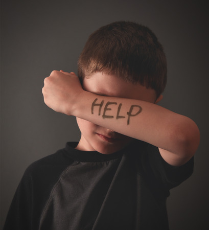 A young child is hiding his eyes with a writing message of help on his arm for a social issue, bully or sadness concept. photo