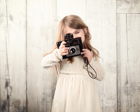 A little child photographer is taking a photo with with an old film camera against a white wood wall for an art or creativity concept.