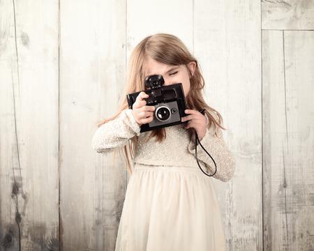 amateur: Un fotógrafo poco niño está tomando una foto con una cámara con película antigua contra una pared de madera de color blanco para un concepto de arte o creatividad. Foto de archivo