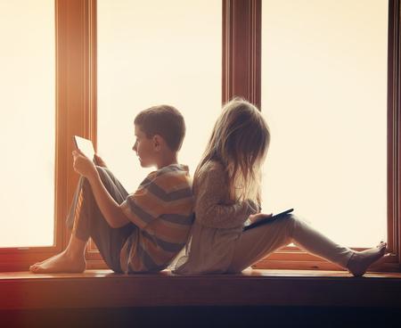 technology: Duas crianças estão sentando-se perto da janela em casa jogando em seus tablets de tecnologia com jogos e aplicativos para um conceito de entretenimento. Imagens