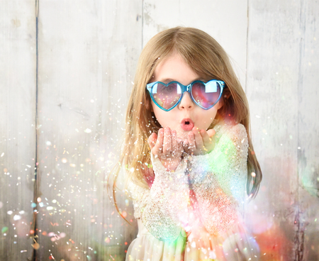 A little child is wearing sunglasses and blowing magical rainbow glitter sparkles in the air for a celebration, happiness or party idea. Stock Photo
