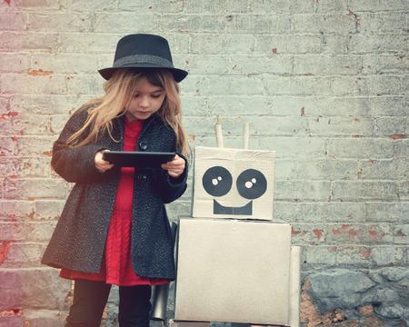 Een klein hipster kind is het dragen van een koele hoed en houden van een tablet met haar stuk speelgoed robot vriendin de stad in voor een geluk of technologie concept.
