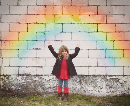 hope: A happy little girl is standing against an old brick wall with a colorful rainbow and her heands are raised for a fun weather outlook concept.