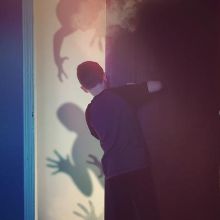 Un bambino spaventato è alla ricerca all'interno di una camera da letto armadio a neri cattivi fantasmi di mostri in background per l'immaginazione o fantasma concetto Archivio Fotografico