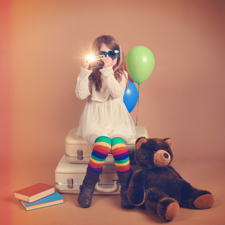 A photo of a vintage child taking a picture with an old camera against with rainbow balloons and a teddy bear for a creativity, art or vision concept.