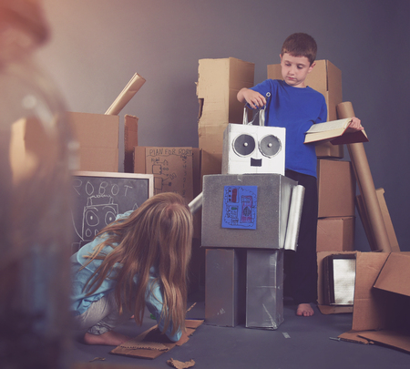 Two Children are building a metal robot with tools and books for an imagination, science or education concept. Фото со стока