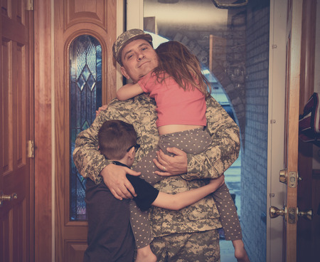 An army soldier man is coming home in the door and hugging his children for a love, family or reunited concept.