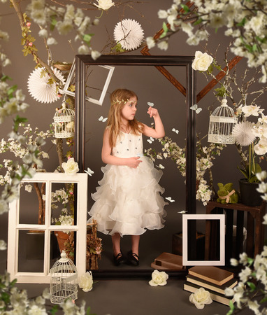 formal garden: A little girl is standing with white butterflies in a spring garden with flowers. The child is standing inside a picture frame with birdcage decorations. Stock Photo